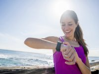 Young woman running outdoors by the beach using a smart watch to check her pulse and calorie countdown